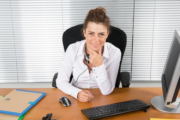 Kobiety brunetka przy biurem w nowożytnym budynku