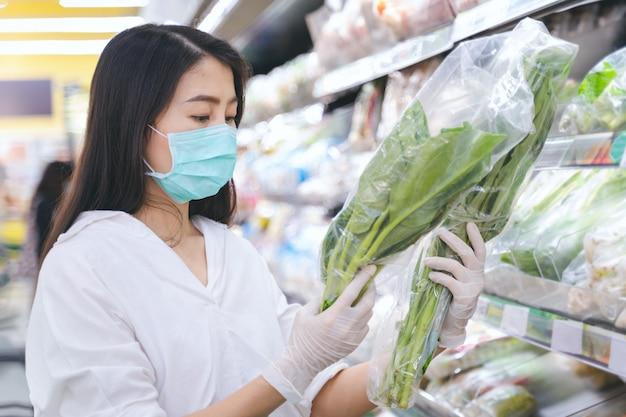 Kobiety być ubranym gacenia twarzy maskę i gumowe rękawiczki robi zakupy jedzenie, owoc i warzywo w spożywczym wydziałowym sklepie.