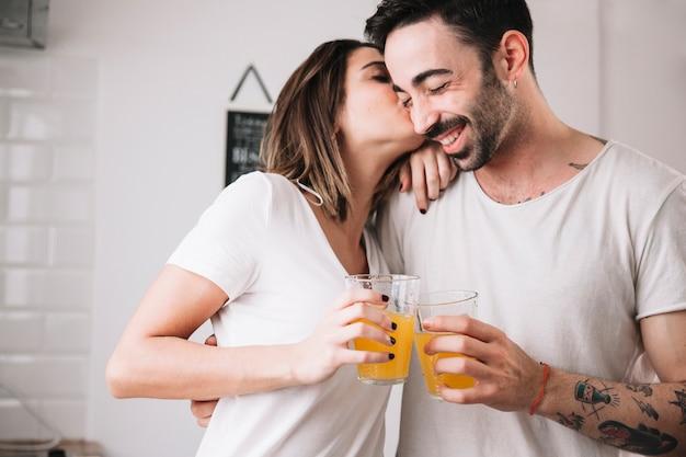 Kobiety całowania mężczyzna podczas gdy cieszący się sok