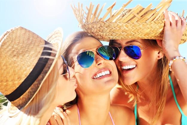 Kobiety całujące przyjaciela na imprezie na plaży