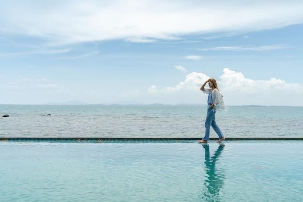 Kobiety chodzą po plaży nad morzem, chmura i błękitne niebo jest niekończącym się tłem