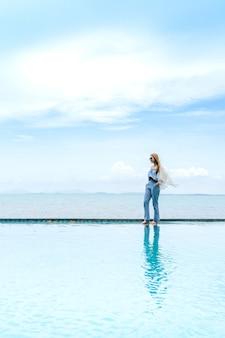 Kobiety chodzą po plaży nad morzem, chmura i błękitne niebo jest niekończącym się tłem.