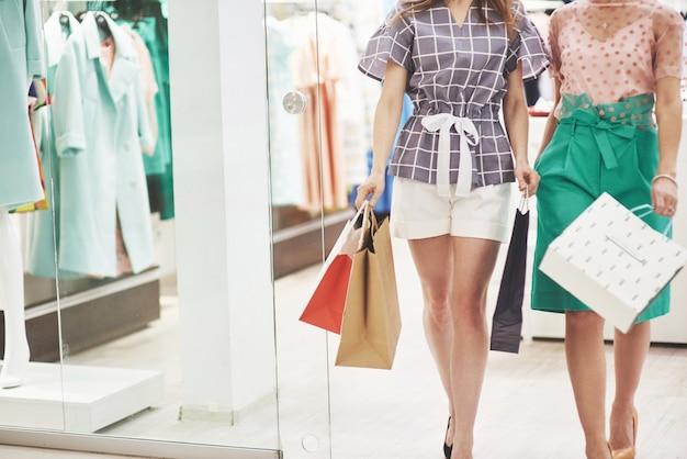 Kobiety chodzą z torbami podczas zakupów w centrum handlowym.