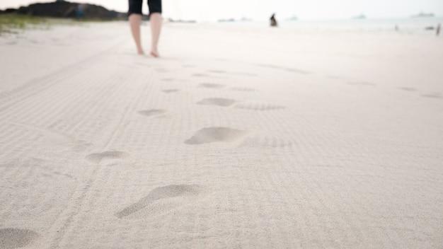 Kobiety chodzące na plaży bosymi stopami z miejsca na kopię i wybierz punkt ostrości.