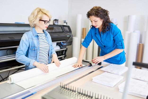 Kobiety cięcia papieru w drukarni