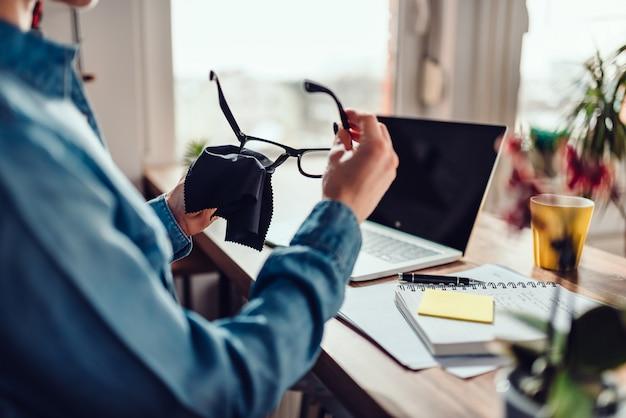 Kobiety cleaning eyeglasses przy jej biurem