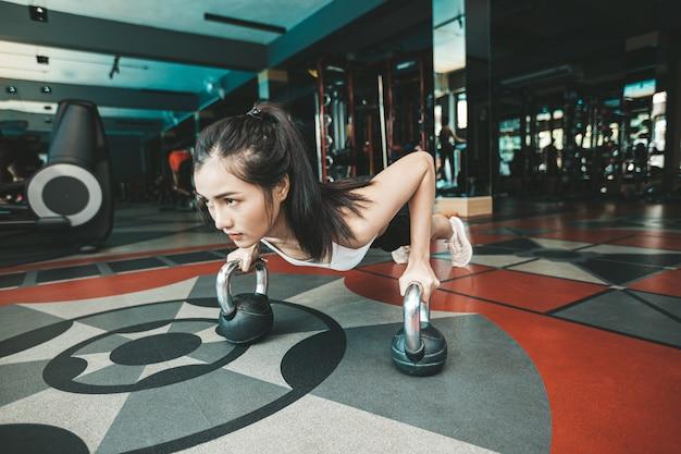 Kobiety ćwiczą pchając podłogę za pomocą kettlebell na siłowni.