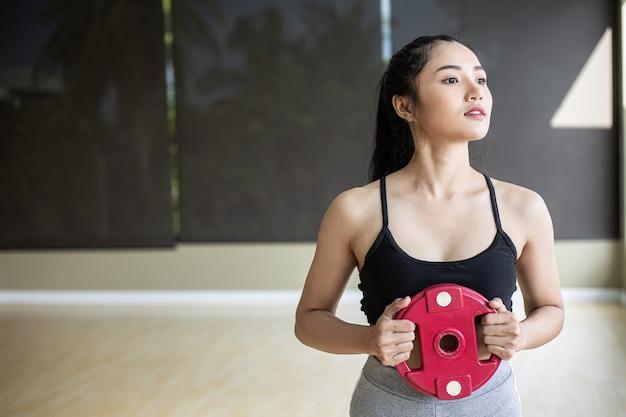 Kobiety ćwiczą z hantlami na klatce piersiowej.