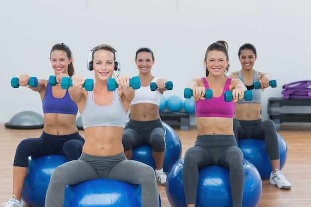 Kobiety ćwiczy z dumbbells na sprawności fizycznych piłkach