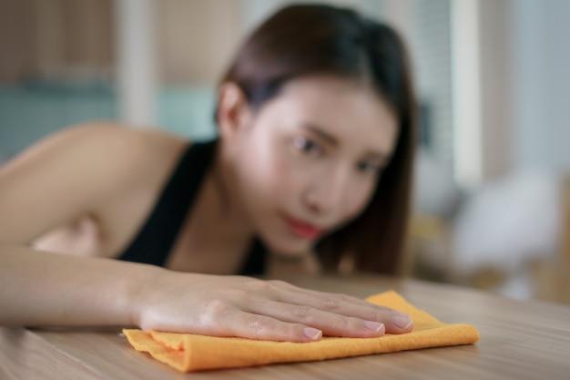 Kobiety czyszczące środek dezynfekujący stół