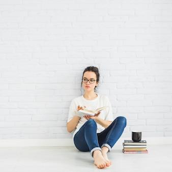 Kobiety czytelnicza książka blisko filiżanki