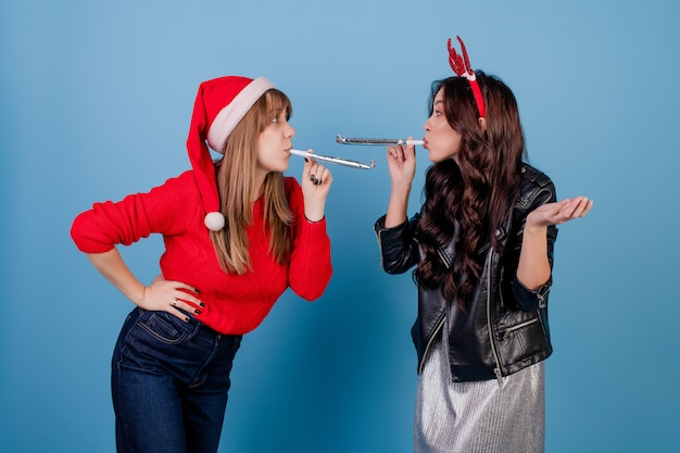 Kobiety dmucha chirstmas gwizdki i jest ubranym boże narodzenie kapelusz odizolowywającego nad błękitem