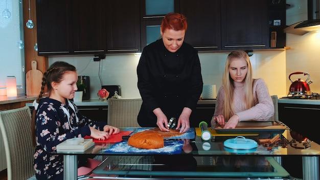 Kobiety do pieczenia pierników w kuchni w domu. młoda dziewczyna pomagając im i obserwując proces.