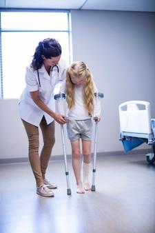 Kobiety doktorska pomaga dziewczyna chodzić z szczudłami w oddziale