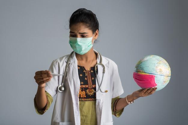 Kobiety doktorska trzyma ziemska kula ziemska dla prezentować wybuchu pandemii wirusa na całej planecie. prezentacja globalnego ocieplenia i wzrostu temperatury.