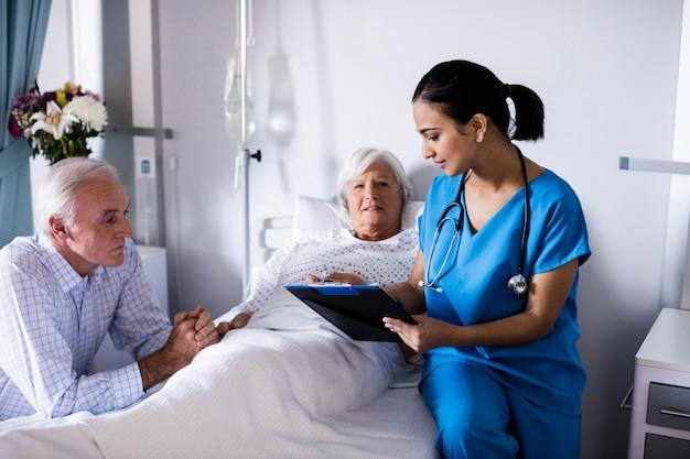 Kobiety doktorski dyskutować z starszą parą nad raportem w oddziale