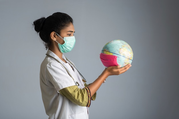 Kobiety doktorski mienie światowa kula ziemska z medycyny twarzy maską. światowa epidemia koronawirusa.
