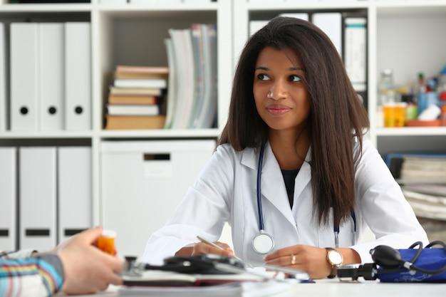 Kobiety doktorski ono uśmiecha się przy jej biurem
