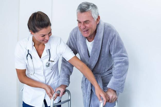 Kobiety doktorski pomaga starszy mężczyzna chodzić z piechurem