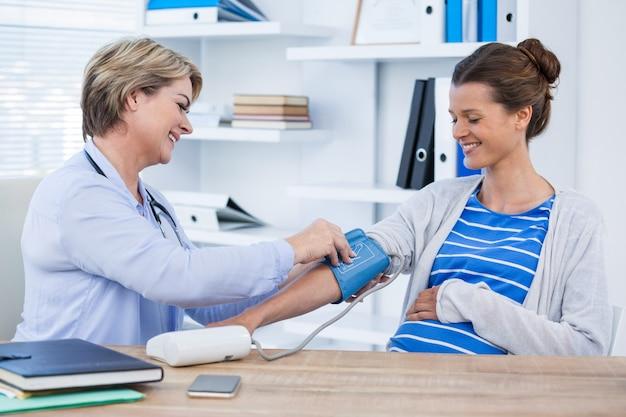 Kobiety doktorski sprawdza ciśnienie krwi pacjent