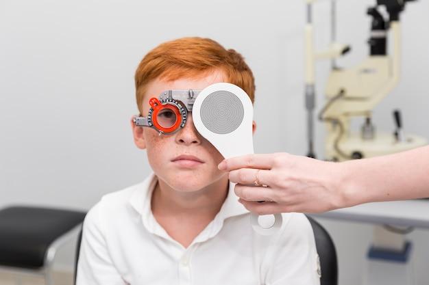 Kobiety doktorski sprawdza wzrok pieg chłopiec z optometrist próby ramą w klinice