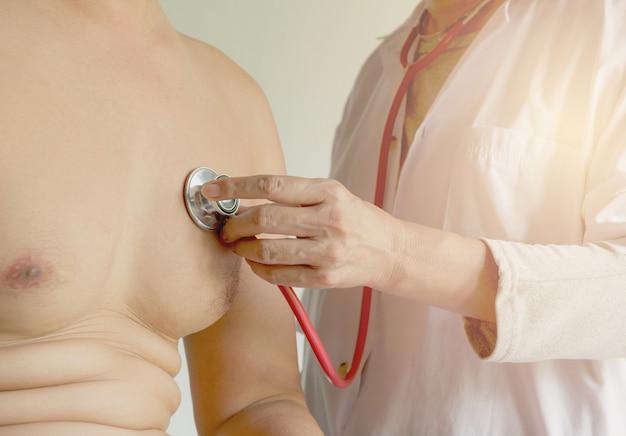 Kobiety doktorski używa stetoskop dla czeka i słucha serce i płuca pacjent
