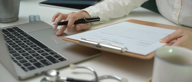 Kobiety doktorski writing świadectwo medyczne na laptopie podczas gdy patrzejący informację na cierpliwej mapie
