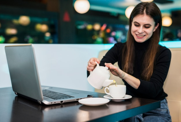 Kobiety dolewania herbata w filiżankę przy stołem z laptopem