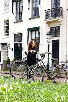 Kobiety dziewczyna parkuje rocznika rowerowego ulicznego starego miasta sity czarnego żakieta długie kędzierzawe włosy cieszy się słońce wiosny szkieł bielu dom