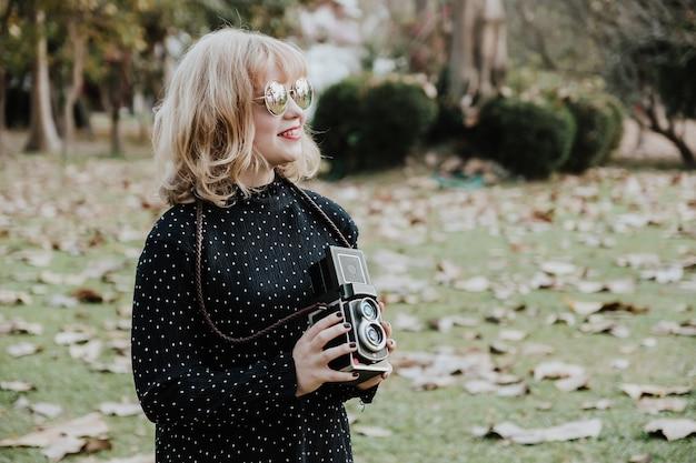 Kobiety fotografii smilling, pozycja i ręka trzyma retro kamerę w plenerowym. rocznika brzmienie