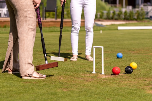 Kobiety grające w krokieta uderzające piłkę młotkiem