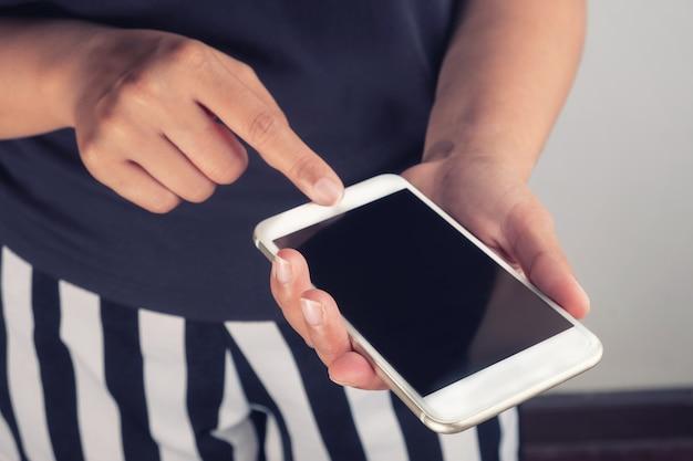 Kobiety i inteligentny telefon w ręku w pokoju