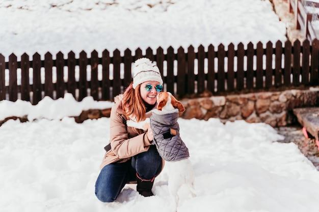 Kobiety i jack russell pies bawić się outdoors przy górą. sezon zimowy