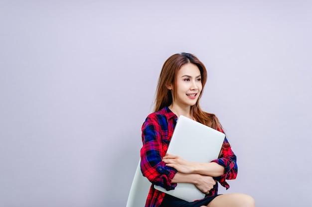 Kobiety i laptopy siedząc i obejmując laptopa z radością w pracy koncepcja prowadzenia sprawnego biznesu.