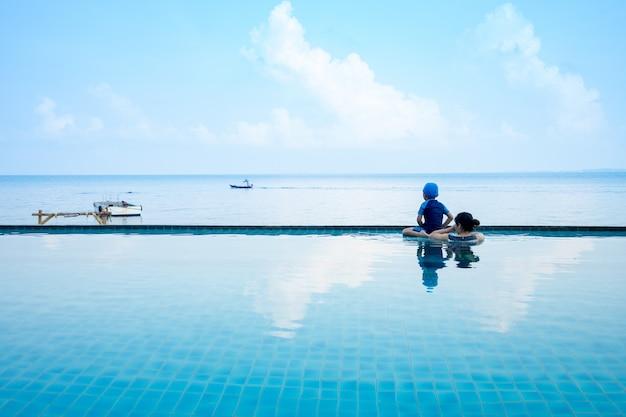 Kobiety i shild w basenie patrząc na łódź na morzu, wakacje na obozie letnim