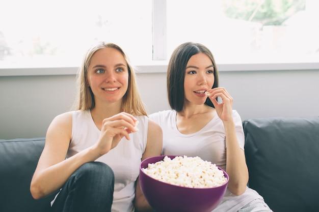 Kobiety jedzące popcorn i oglądające telewizję