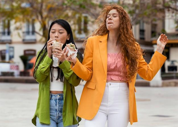 Kobiety jedzące uliczne jedzenie na świeżym powietrzu