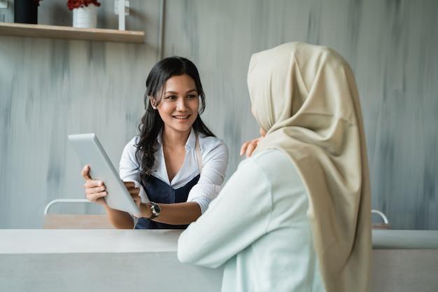 Kobiety kelnerka pokazuje menu kobieta klient