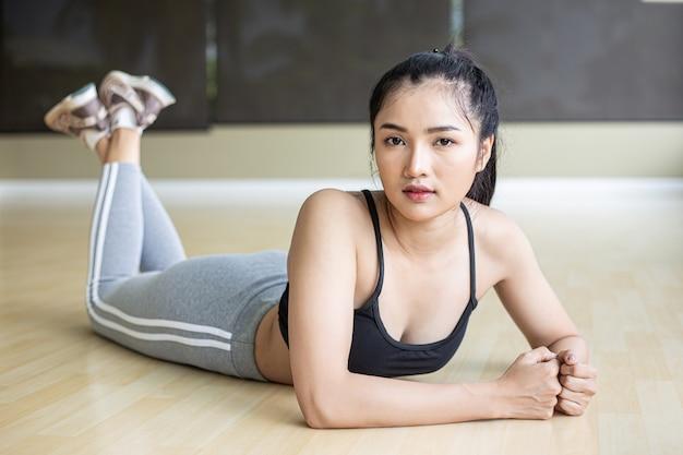 Kobiety kładą się, relaksują i podnoszą nogi na siłowni.