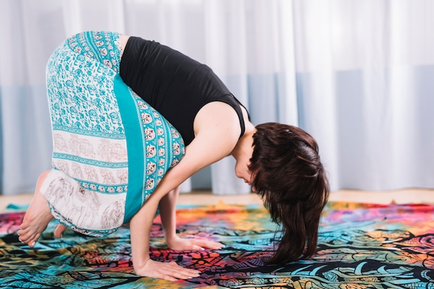 Kobiety kobieta robi bakasana joga pozie w domu
