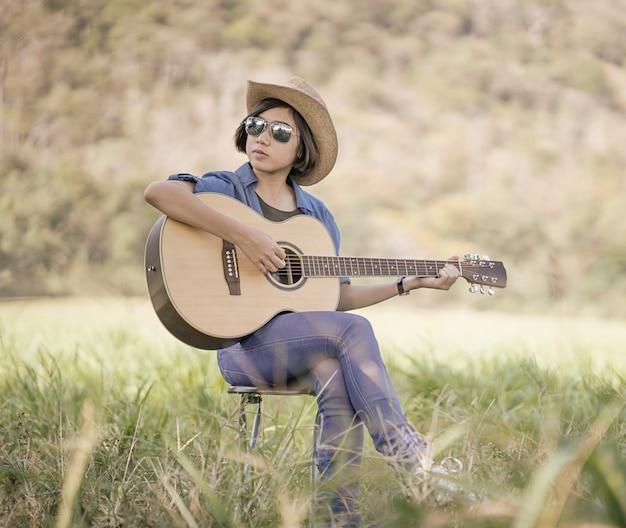 Kobiety krótkie włosy noszą kapelusz i okulary przeciwsłoneczne siedzą, grając na gitarze w polu trawy