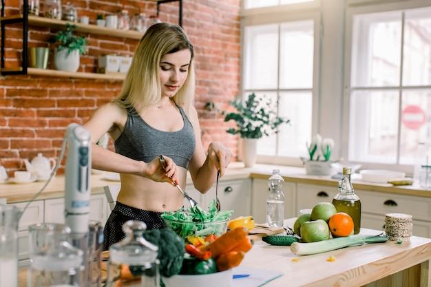 Kobiety kucharstwo w nowej kuchni robi zdrowemu jedzeniu z warzywami. młoda kaukaska kobieta po dwudziestce