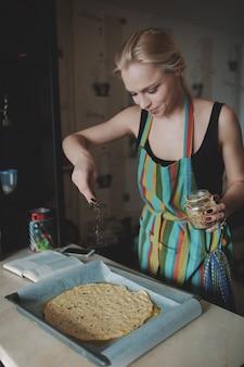 Kobiety kulinarna pizza przy kuchnią