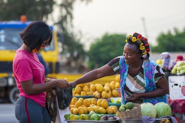 Kobiety kupują owoce na targu