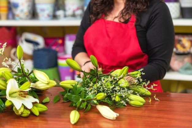 Kobiety kwiaciarnia jest ubranym fartuch pozycję przy kontuarem robi bukietowi dla klienta przy kwiatu sklepem.