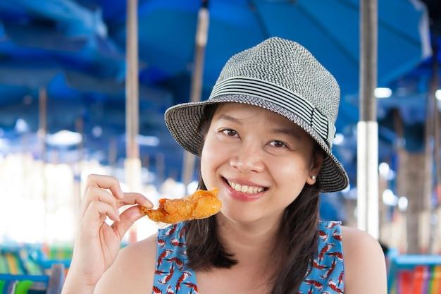 Kobiety łasowania owoce morza outside w lata ono uśmiecha się. azjatycka kaukaska dziewczyna je zdrowych świeżych owoce morza.