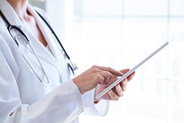 Kobiety lekarka używa jej cyfrową pastylkę w biurze.