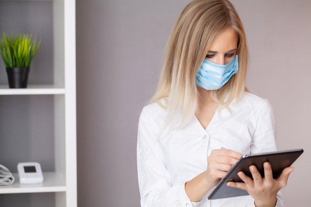 Kobiety lekarka w ochronnej masce pracuje przy pastylką w biurze