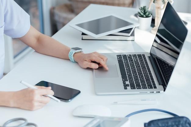 Kobiety lekarka wręcza trzymać laptop i używać komputer na stole w medycznym pokoju przy szpitalem