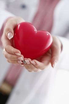 Kobiety lekarki chwyt w ręce i okładkowa czerwieni zabawka